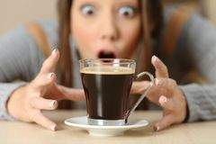 Amazed woman looking at coffee cup. Front view portrait of an amazed woman looking at coffee cup Stock Photography