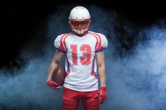Front view portrait of american football player wearing helmet with ball against white smoke royalty free stock photography