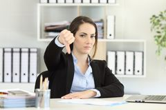 Businesswoman denying with thumbs down. Front view portrait of an angry businesswoman denying with thumbs down at office Stock Photography