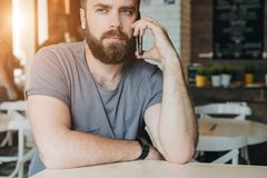 Front view. Portrait of attractive young bearded hipster man sitting in cafe at table and talking on his cell phone. Blurred background, film effect.Telephone Stock Photography