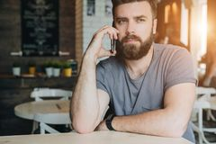 Front view. Portrait of attractive young bearded hipster man sitting in cafe at table and talking on his cell phone. Telephone conversations. Guy is calling Stock Photo