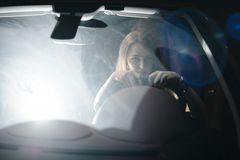 Front view. Portrait of beautiful woman driving her luxury car at night. The traffic lights behind stock photos