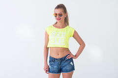 Front view portrait of beautiful model posing in a trendy summer outfit, wearing bright yellow t-shirt, sunglasses Stock Photo