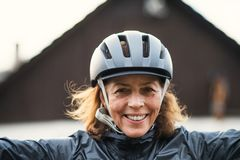 A front view portrait of cheerful active senior woman standing outdoors. A front view portrait of cheerful active senior woman standing outdoors in front of a stock photo