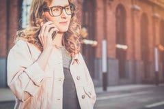 Front View Portrait de jeune femme en verres se tenant dehors et parlant au téléphone portable Images libres de droits