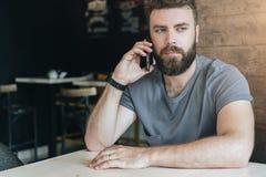 Front View Portrait du jeune homme barbu bel de hippie s'asseyant en café à la table et parlant à son téléphone portable Image stock
