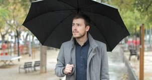 Frustrated man complaining about bad weather. Front view portrait of a frustrated man walking in a park complaining about bad weather in a rainy day of winter stock video