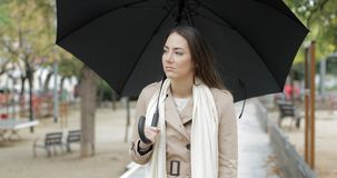 Frustrated woman walking complaining under the rain. Front view portrait of a frustrated woman walking holding an umbrella complaining under the rain in winter stock video