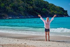 Front view portrait a happy boy breathing deep fresh air and outstretching arms with the tropical sea bay on the background. Child raising arms on the sea stock photo