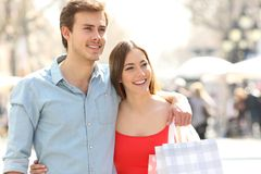 Happy couple of shoppers walking in the street royalty free stock images