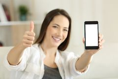 Female showing a blank smart phone screen at home. Front view portrait of a happy female showing a blank smart phone screen at home royalty free stock photos