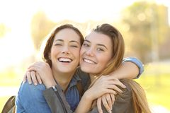 Happy friends with perfect smile cuddling looking at you royalty free stock images