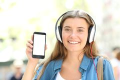 Girl with headphones showing blank smart phone screen. Front view portrait of a happy girl with headphones showing blank smart phone screen in the street Royalty Free Stock Photos