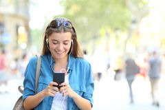 Happy girl listening to music using a phone. Front view portrait of a happy girl listening to music using a smart phone walking towards camera with copy space at Stock Photography
