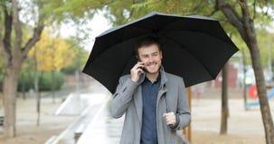 Happy man talking on phone walking under the rain stock video footage