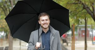 Happy man walking under the rain looking at you. Front view portrait of a happy man walking in a park under the rain holding an umbrella looking at you in winter stock video footage