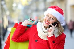 Happy shopper with shopping bags calling on phone in christmas Stock Image