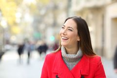 Happy woman in the street looking at side in winter. Front view portrait of a happy woman in red in the street looking at side in winter stock photography
