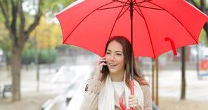 Happy woman talking on phone under the rain stock video