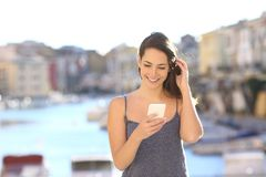 Happy woman using a smart phone in a coast town. Front view portrait of a happy woman using a smart phone in a coast town street royalty free stock photo
