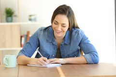 Woman writing in a notebook on a table Royalty Free Stock Image