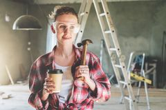 Front view. Portrait of happy young female construction worker, carpenter, repairman standing in workshop. Wearing safety glasses, holding hammer and cup of Stock Image
