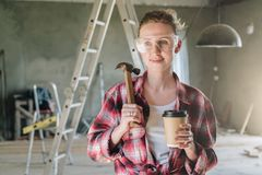 Portrait of happy young female construction worker, carpenter, repairman standing in workshop wearing safety glasses Royalty Free Stock Images