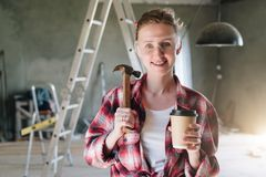 Front view. Portrait of happy young female construction worker,. Carpenter, repairman standing in workshop wearing safety glasses, holding hammer and cup of royalty free stock photos