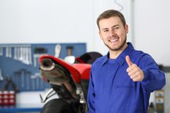 Motorbike mechanic with thumb up in a workshop. Front view portrait of a motorbike mechanic looking at camera with thumbs up in a mechanical workshop Stock Photography