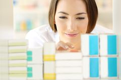 Relaxed pharmacist searching medicines in a pharmacy Royalty Free Stock Photos
