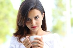 Beautiful woman holding coffee cup looks at you stock images