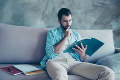 Front view portrait of serious man with bristle, looking in book. Reading book, learning english, sitting on couch at home, holding hand near chin royalty free stock images