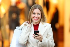 Shopper holding shopping bags and phone looking at you Stock Image