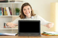 College student showing a blank laptop screen. Front view portrait of a single happy college student showing a blank laptop screen on a table at home stock photography