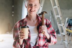 Front view. Portrait of smiling female construction worker, carp. Enter, repairman standing in workshop wearing safety glasses, holding hammer and cup of coffee Royalty Free Stock Images