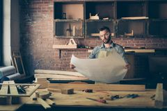 Front view portrait of thoughtful minded serious pensive confide. Nt concentrated furniture maker wearing checkered casual shirt apron and protective glasses, he Stock Image