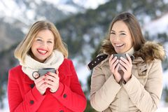 Two friends posing in winter looking at camera. Front view portrait of two friends posing in winter looking at camera in a snowy mountain stock photography