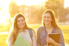 Two happy students looking at camera at sunset royalty free stock images