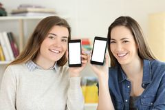 Two students showing to camera smart phone screens. Front view portrait of two happy students showing to camera smart phone screens mockup Royalty Free Stock Image