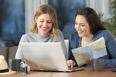 Tourists planning travel in an apartment. Front view portrait of two happy tourists planning travel in an apartment Royalty Free Stock Photo