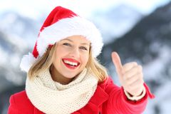 Woman on christmas holidays with thumbs up. Front view portrait of a woman wearing santa claus hat on christmas holidays with thumbs up with a snowy mountain in royalty free stock images