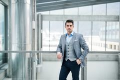 A front view of portrait of young businessman indoors in an office. A front vire of portrait of young businessman indoors in an office. A close-up stock photography