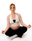 Front view of pregnant female doing meditation Stock Images