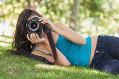 Front view of pretty brunette woman lying on a lawn taking a picture Royalty Free Stock Images