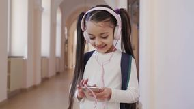 Pretty girl in pink headphones and listening music in school. Front view of pretty longhaired girl in white shirt wearing pink headphones and listening music in stock video footage
