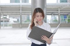 Front view of pretty young Asian business woman talking on phone and looking document file in her hands at outside office. Front view of pretty young Asian stock photography