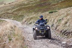 Front view of quad bike zipping along a country road royalty free stock photography
