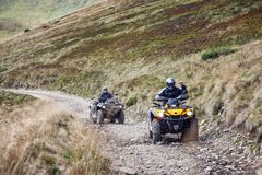 Front view of quad bikes zipping along a country road stock photo