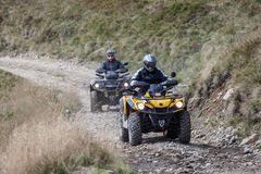 Front view of quad bikes zipping along a country road royalty free stock image