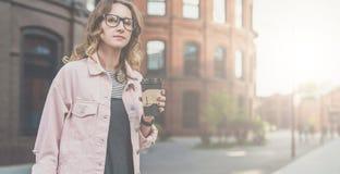 Front View Retrato da jovem mulher nos vidros que estão fora e que guardam uma xícara de café imagem de stock